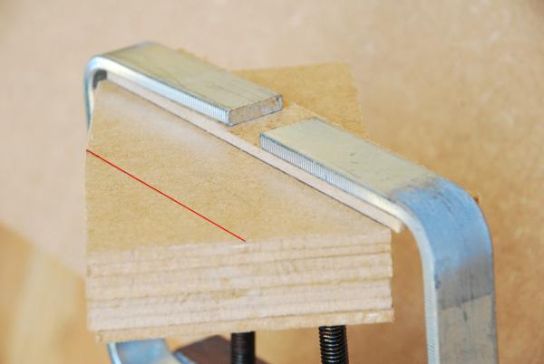 Nous plaçons cet assemblage sous un étau. Nous traçons un second repère parallèle au tracé de l'hypoténuse de nos triangles. La distance entre ces deux droites correspond à la distance entre la lame et le bord du sabot de notre scie sauteuse.