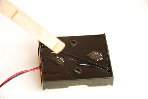 Nous pouvons a présent fixer notre dispositif à l'intérieur de la boîte. Ici, nous posons deux pointes de colle sur notre support de piles.