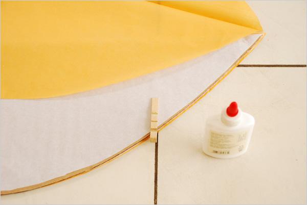 Lorsque le séchage est complet, nour retirons le patron en carton et nous le plaçons sur le fuseau blanc que nous replions dessus. Nous présentons alors un nouveau fuseau orange déplié que nous collerons au fuseau blanc, sur le bord extérieur, comme précédemment.