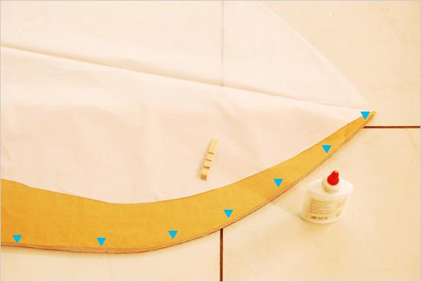 Nous commençons l'assemblage des pans de papier. Sur un bord du fuseau orange plié, dans lequel nous avons inséré le patron en carton pour éviter tout contact avec son repli, nous allons appliquer un mince filet de colle (suivant les repères bleus). Nous viendrons ensuite positionner un des bords de notre fuseau blanc, déplié.
