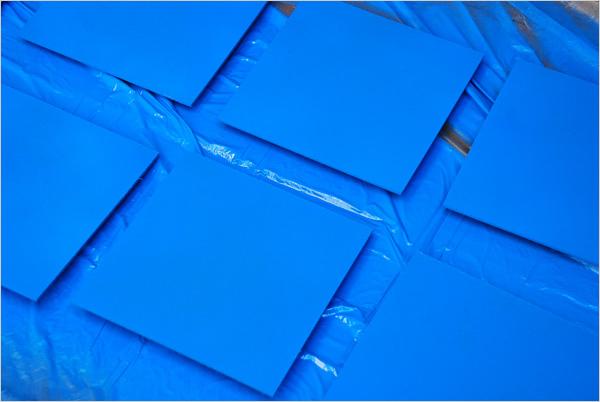 Ensuite, ces plaques sont peintes simultanément avec du bleu de mer. Nous avons pris soin de détacher les plaques du sol en glissant sous chacune d'entre elles un support en bois. Cela permet de peindre également les côtés en évitant que nos plaques ne collent au sol après séchage.